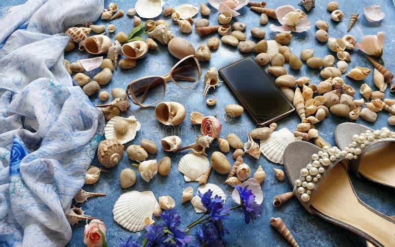 在蓝色背景,海洋海洋夏天海假日sunglass电话白色凉鞋的贝壳成珠状海滩自然背景 免版税库存图片