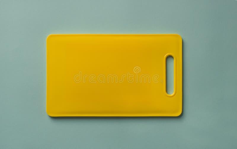 在蓝色背景,顶视图的黄色塑料切板 图库摄影