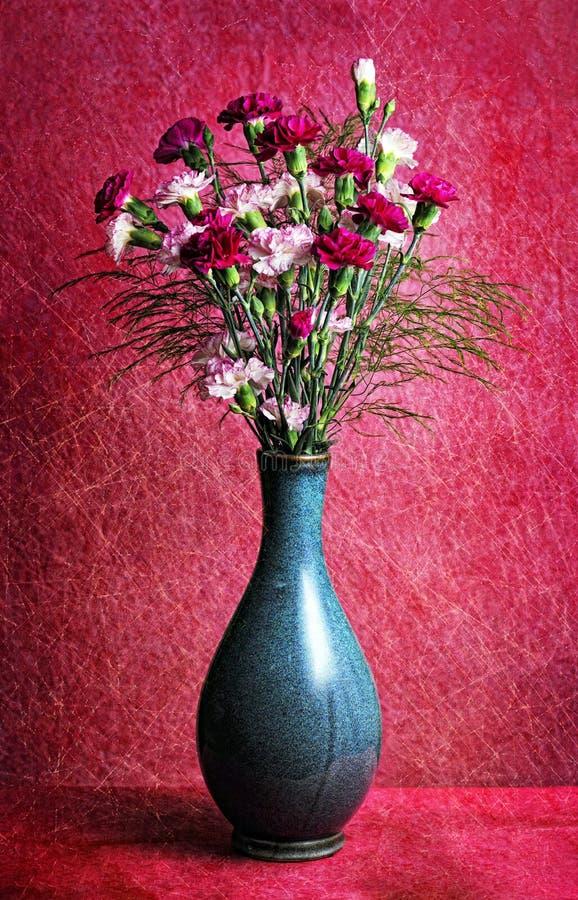 在蓝色花瓶的桃红色和红色康乃馨在桃红色背景、花背景春天的或复活节 库存图片
