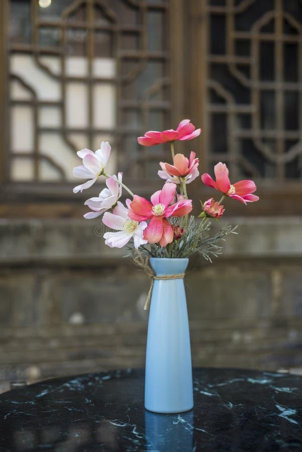 在蓝色苗条瓶的红色和白色小花 免版税库存照片