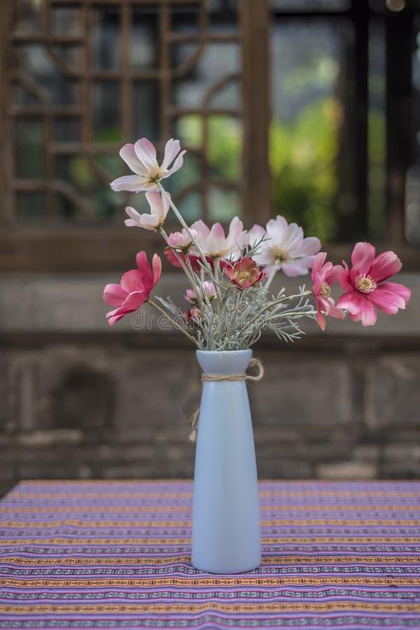 在蓝色苗条瓶的红色和白色小花 库存图片