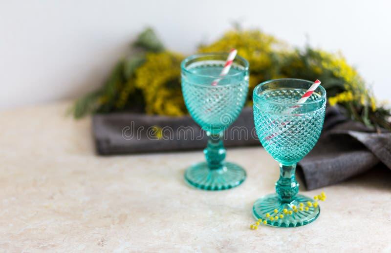 在蓝色葡萄酒觚的Refhesing饮料在与srping的花的白色背景 免版税库存图片