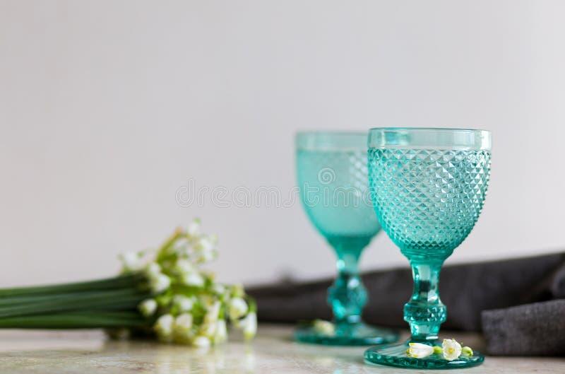 在蓝色葡萄酒觚的Refhesing饮料在与srping的花的白色背景 免版税库存照片