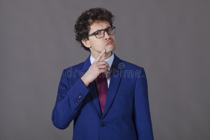 在蓝色衣服的做鬼脸智力的商人 免版税库存照片