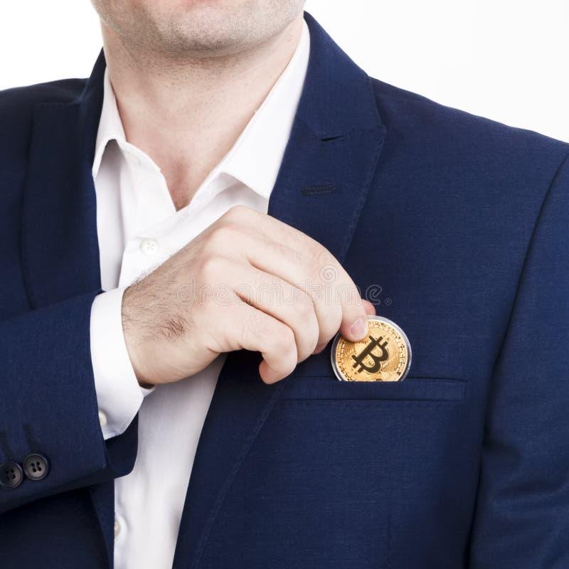 在蓝色衣服的商人投入bitcoin装在口袋里 Cryptocurrency和数字式金钱投资概念 方形的图片,没有面孔,衣服 库存图片