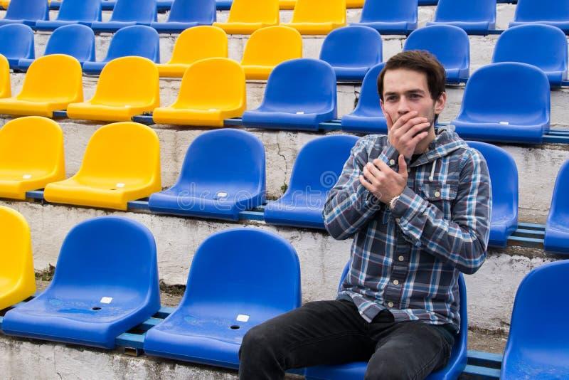 在蓝色衬衣的有吸引力的运动的年轻人模型坐蓝色体育场位子在训练凝视以后在领域 库存图片
