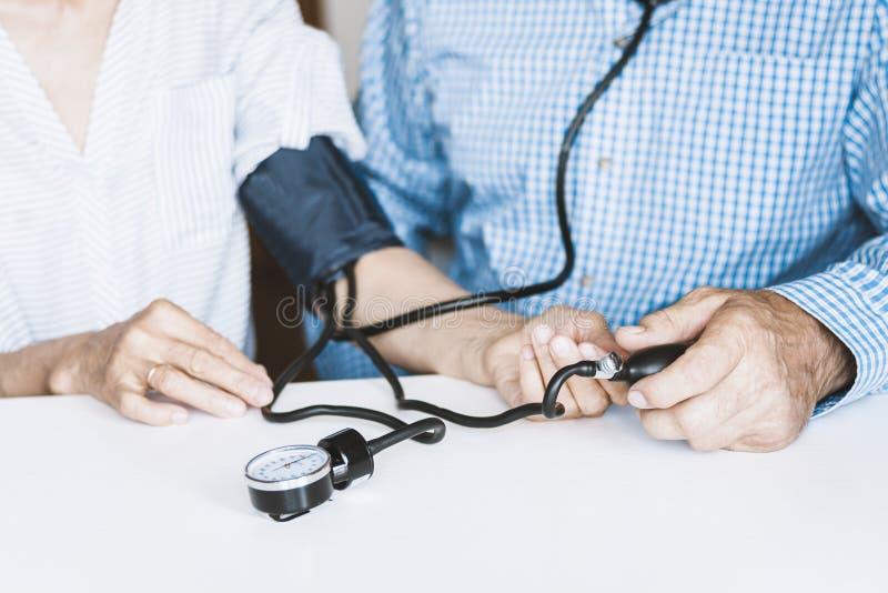 在蓝色衬衣的治疗师男性手有一名妇女的经典tonometer测量的血压在白色桌上的本级教室 图库摄影