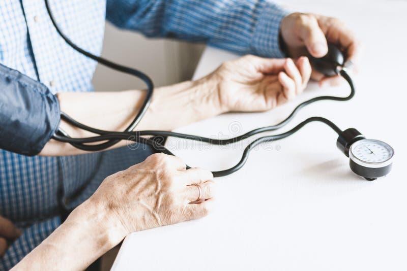 在蓝色衬衣的治疗师男性手有一名妇女的经典tonometer测量的血压在白色桌上的本级教室 免版税库存照片