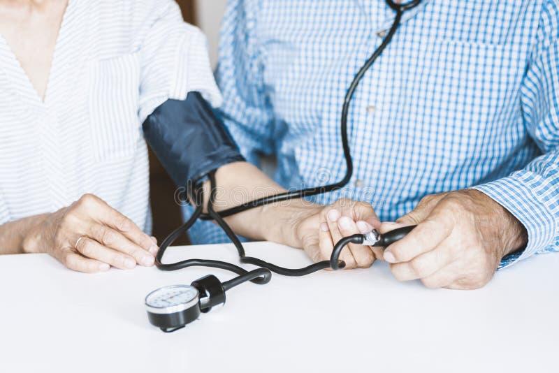 在蓝色衬衣的治疗师男性手有一名妇女的经典tonometer测量的血压在白色桌上的本级教室 免版税库存图片