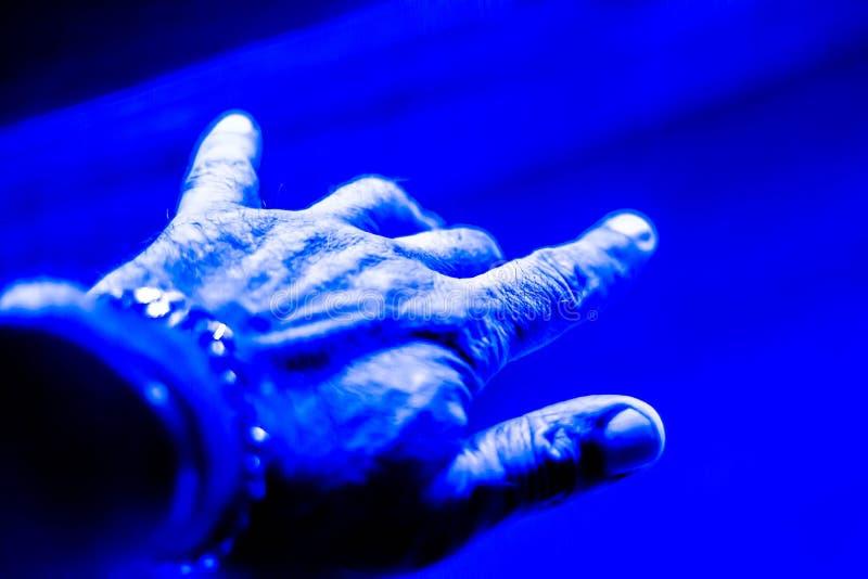 在蓝色被带领的光下的手 LED光现在获取极大的成功,他们的好处许多,在实用  库存图片