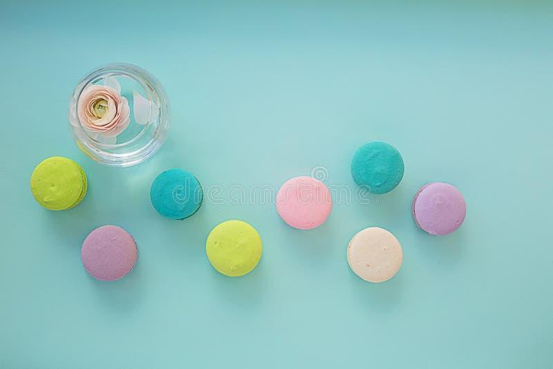 在蓝色质地背景的五颜六色的蛋白杏仁饼干与在花瓶的毛茛属 库存照片