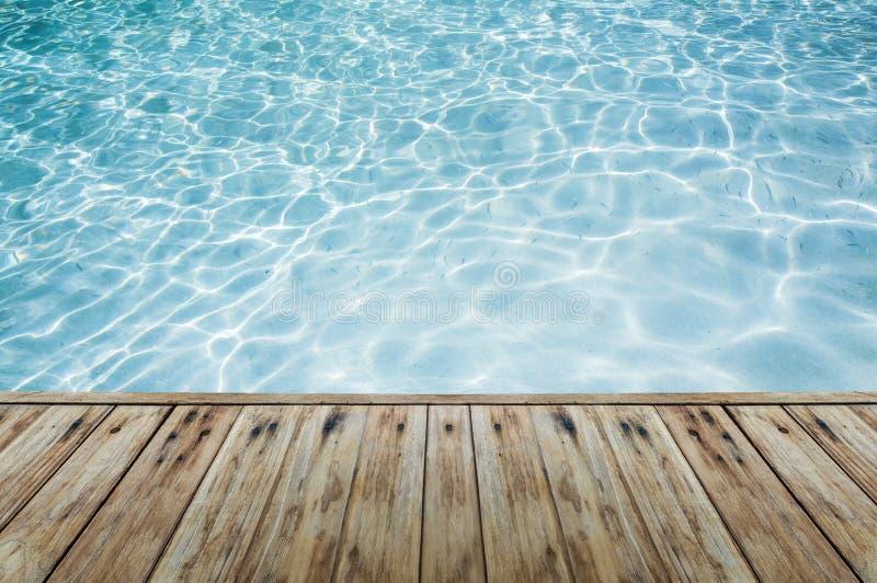 在蓝色透明的水旁边的木地板 免版税图库摄影