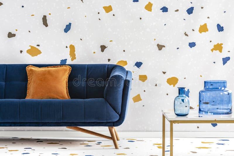 在蓝色长沙发的橙色枕头在与桌和墙纸的五颜六色的客厅内部 实际照片 免版税库存图片