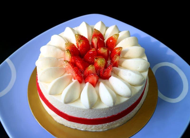 在蓝色陶瓷盘子的味道好的新鲜的草莓香草短小蛋糕 库存照片