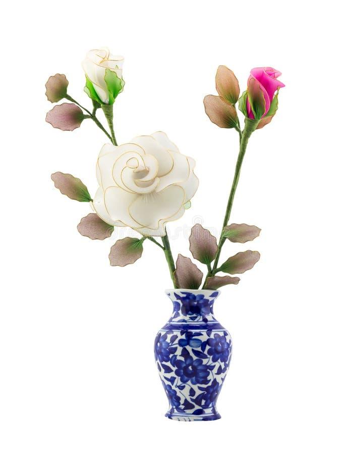 在蓝色陶瓷花瓶的桃红色和白色尼龙织品花在孤立白色背景 库存图片