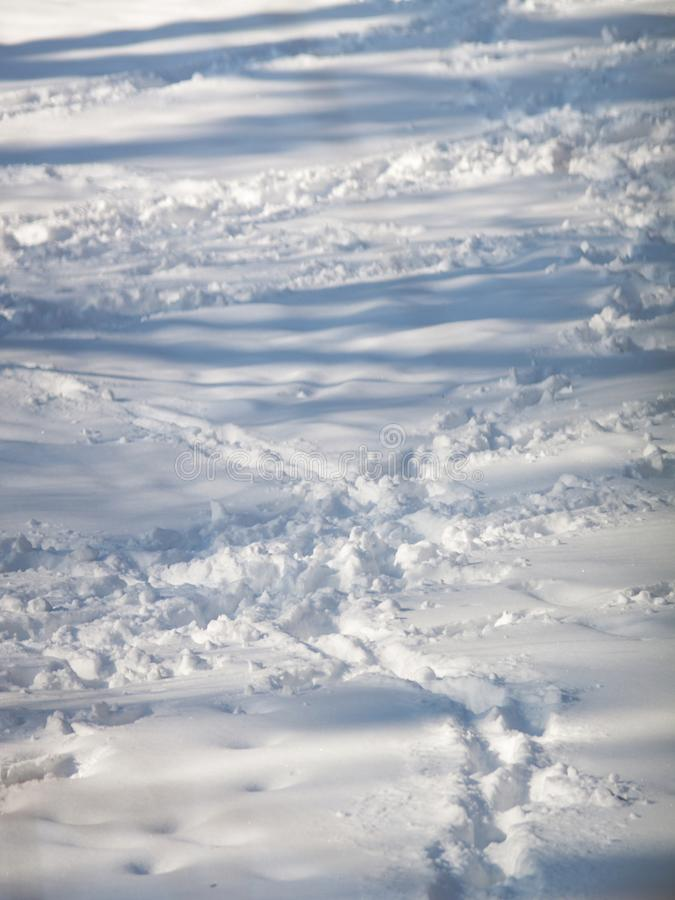 在蓝色雪的人的脚印 免版税库存照片