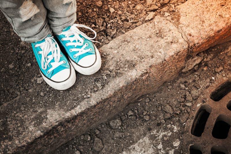 在蓝色鞋子的脚在街道边缘站立 免版税库存照片