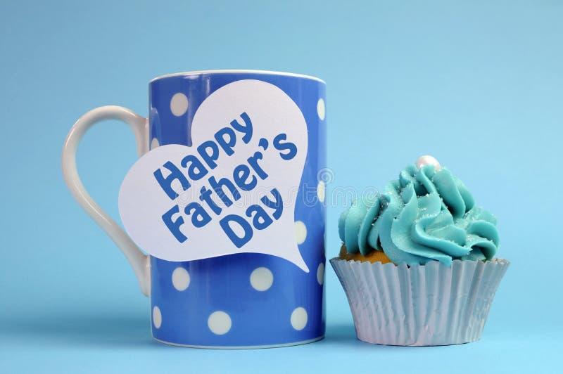 在蓝色题材圆点咖啡杯的愉快的父亲节消息用杯形蛋糕。 图库摄影