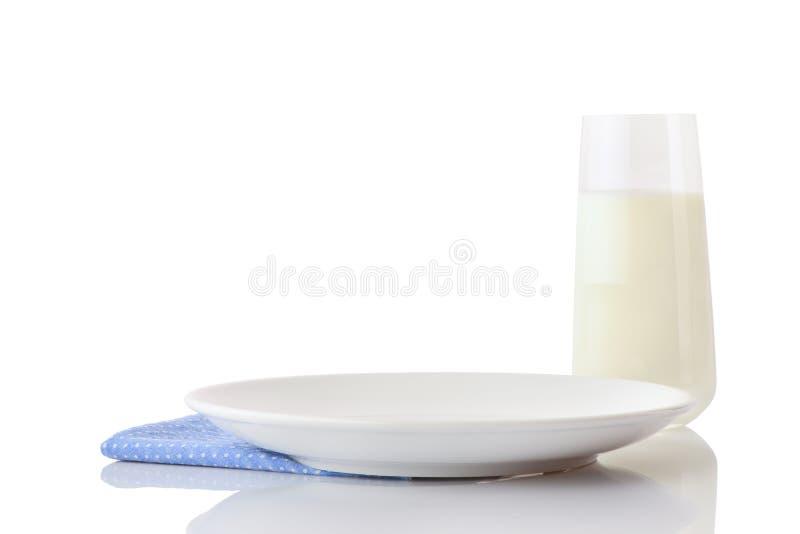 在蓝色餐巾的空的白色陶瓷板材在小白色圆点和杯牛奶 库存照片