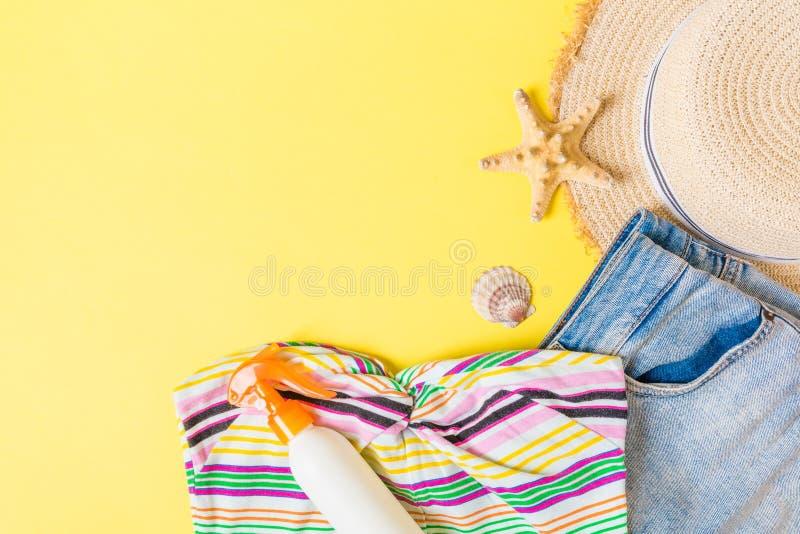 在蓝色黄色背景的妇女夏天成套装备顶视图 时尚假期概念 免版税库存图片