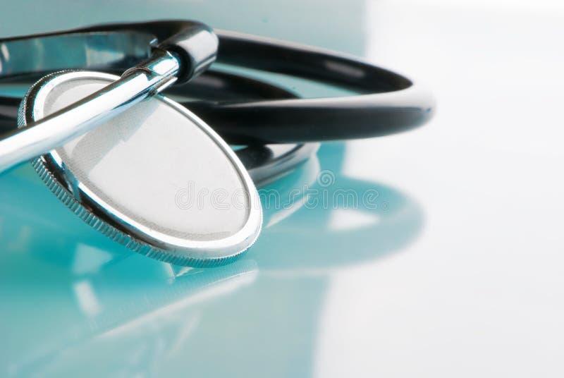 在蓝色,反射性背景的听诊器 免版税库存照片