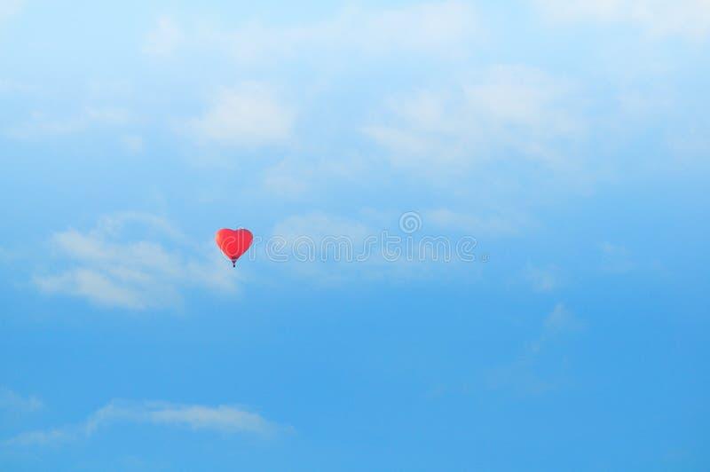 在蓝色晴朗的天空的五颜六色的红色心形的气球飞行 淡色更正 免版税库存照片