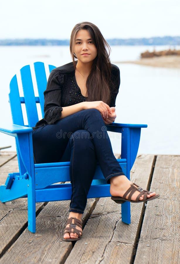 在蓝色adirondak椅子的两种人种的青少年在湖的码头 免版税库存图片
