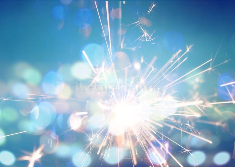 在蓝色bokeh背景的火闪烁发光物 免版税库存图片