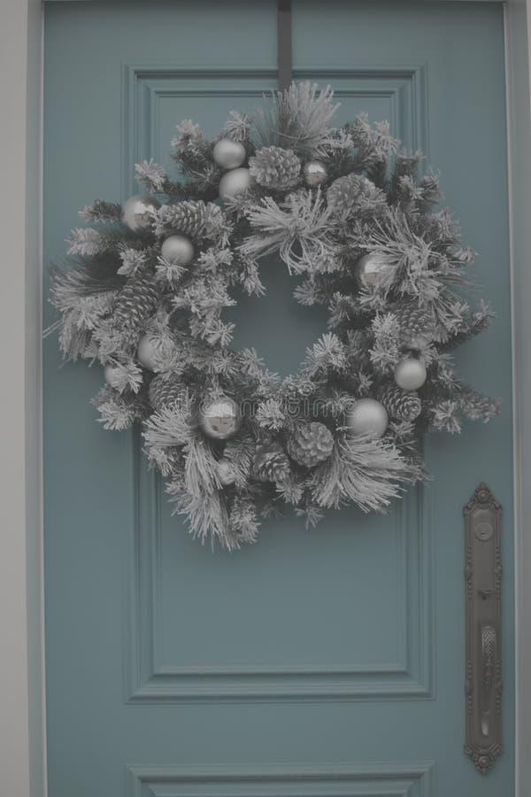 在蓝色dooor的银色圣诞节花圈 库存照片