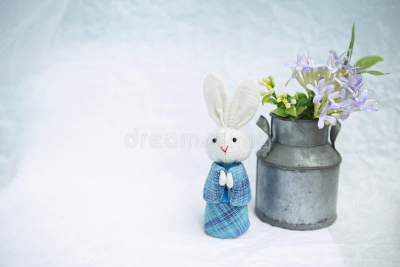 在蓝色Japaneses传统礼服的逗人喜爱的小的兔子玩偶有金属花盆的 库存图片