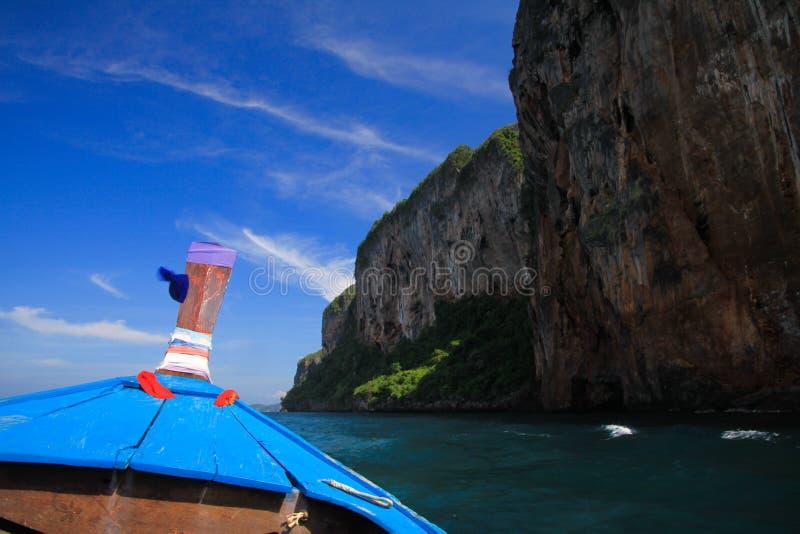 在蓝色longtail小船和岩石墙壁装饰的木弓的看法在天空蔚蓝下与少量卷云 免版税图库摄影