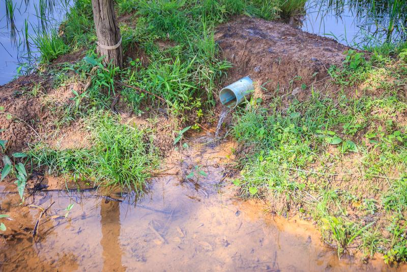 在蓝色PVC排水设备管子的水流量在米农场 农夫半新P 免版税库存照片