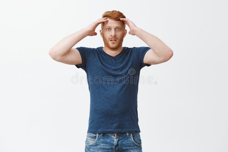 在蓝色T恤杉的沮丧的阴沉的红头发人男性,拿着头和凝视与失望照相机,丢失的赌注 免版税库存图片