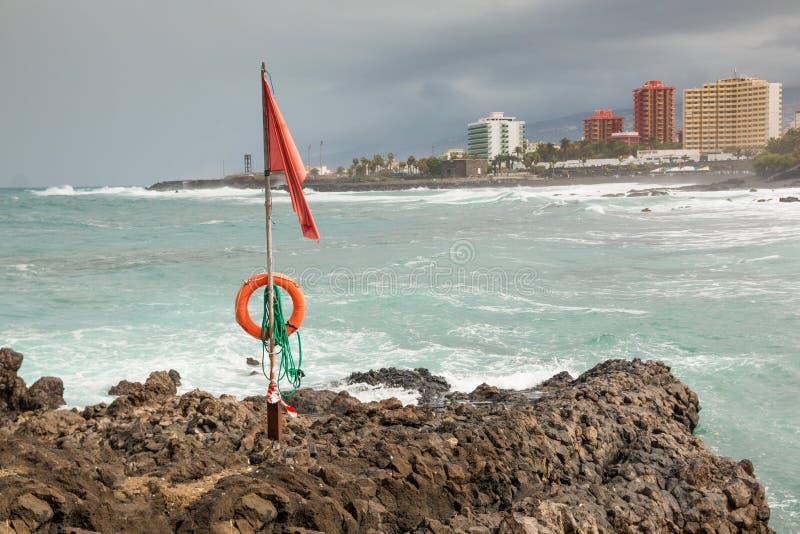 在蓬塔Brava海滩的红旗从海滩的在普埃尔托德拉克鲁斯,特内里费岛 图库摄影