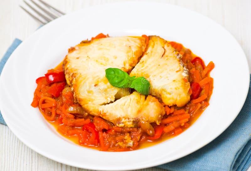 在蕃茄卤汁的烤鱼用红萝卜和红辣椒 免版税库存图片