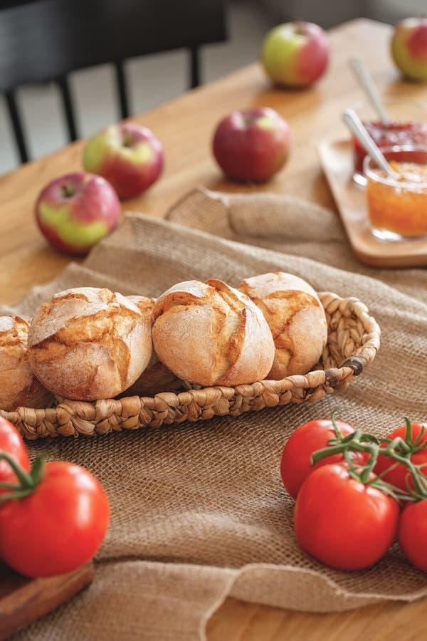 在蕃茄和大面包的特写镜头在木桌上用在餐厅内部的苹果 实际照片 免版税库存照片