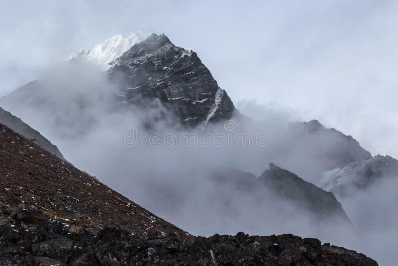 在薄雾的剧烈的黑岩石在著名珠穆琅玛 库存照片