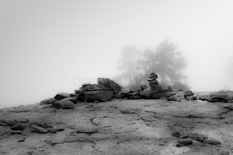 在薄雾的树如被看见在山和岩石土坎  库存图片