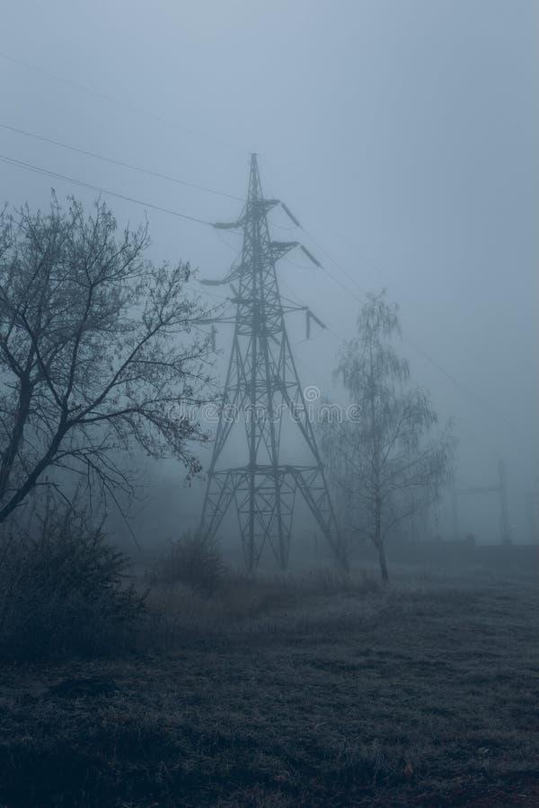 在薄雾的高压杆 免版税库存图片