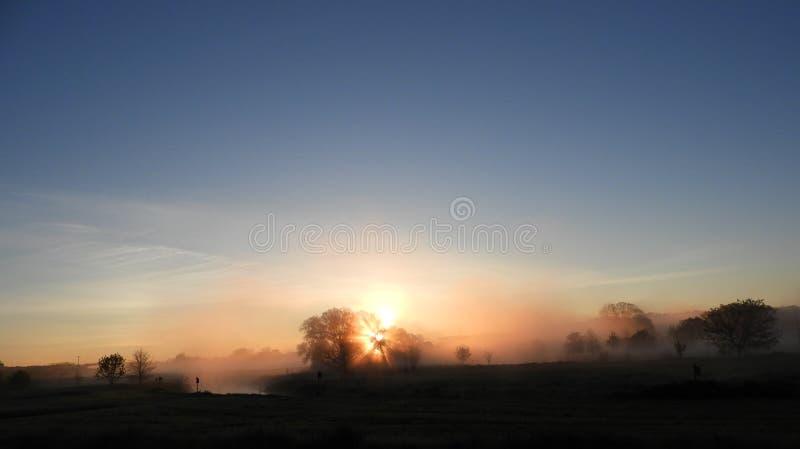 在薄雾被盖的农田小河的日出 库存照片