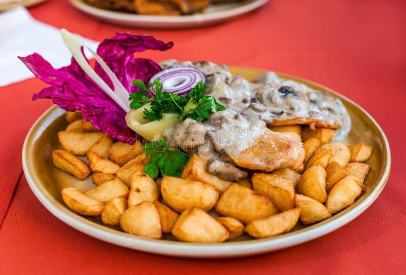 在蘑菇酱油的烤鸡牛排用油煎的土豆楔住 图库摄影