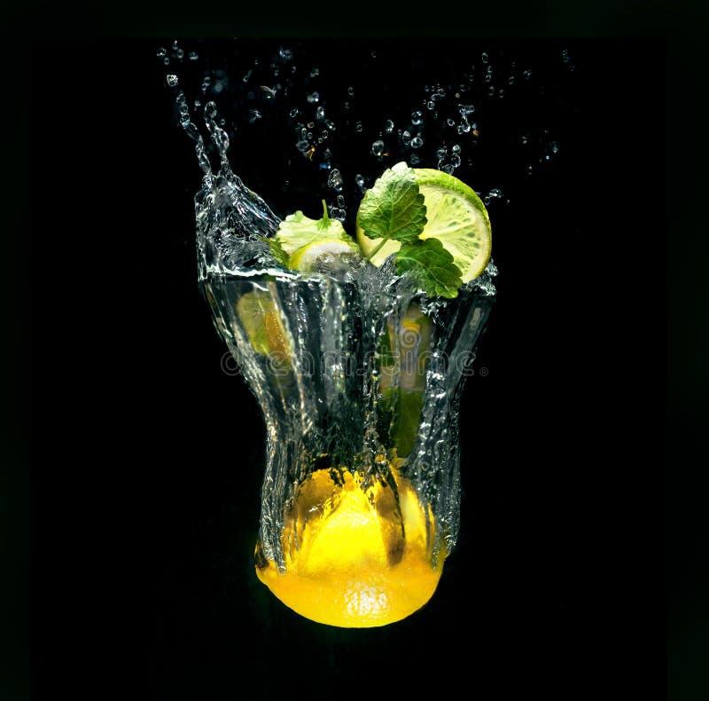 在虚构的玻璃的刷新的鸡尾酒在水外面在黑背景飞溅 免版税库存照片