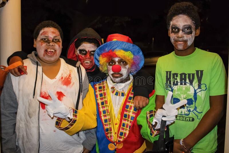 在蛇神面孔油漆的土尔沙美国四非裔美国人的boyss和一穿戴了象小丑givng两和平标志把戏或款待在Ha 库存照片
