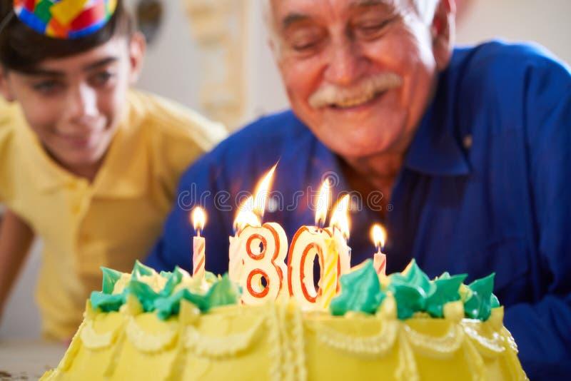 在蛋糕生日聚会的男孩和老人吹的蜡烛 免版税库存图片
