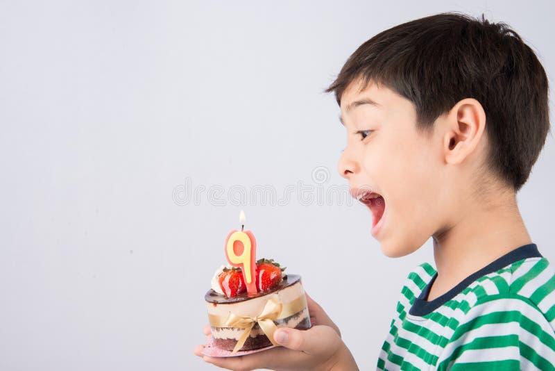 在蛋糕的小男孩吹的蜡烛为他的生日 库存图片