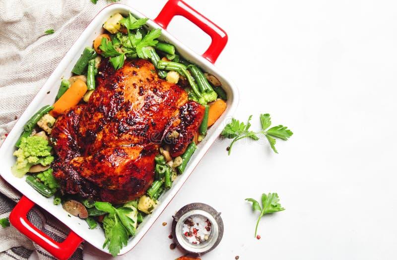 在蜂蜜釉的被烘烤的鸡与菜装饰品,白色背景,顶视图 库存照片