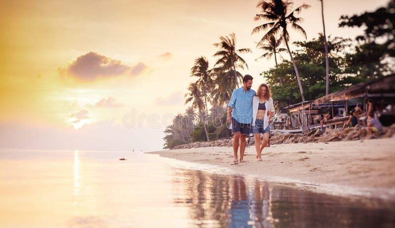 在蜜月假期旅行期间,美丽的年轻人爱愉快的在胳膊的夫妇走的胳膊在海滩在日落 库存照片