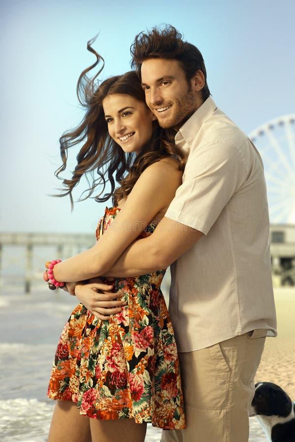 在蜜月的愉快的已婚夫妇绊倒在海滩 库存图片