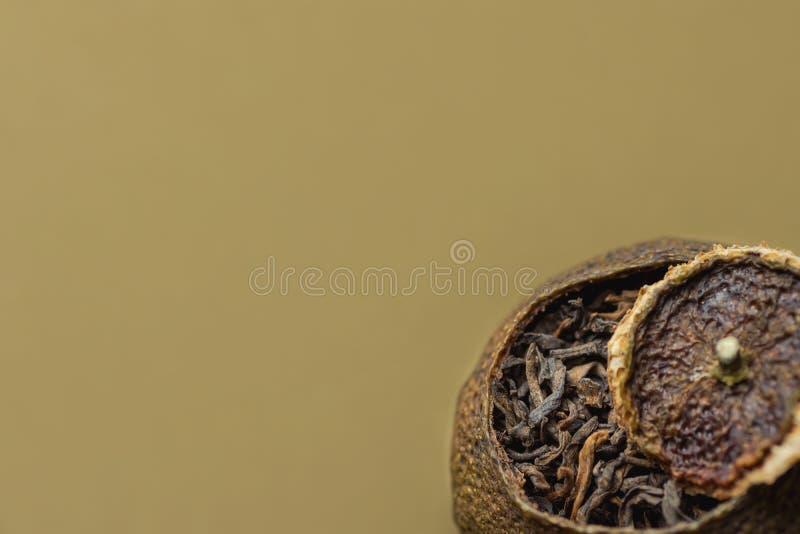 在蜜桔果皮的年迈的被发酵的黑中国人普洱哈尼族彝族自治县茶与盒盖 米黄背景 亚洲烹调健康饮料 关闭 免版税库存图片