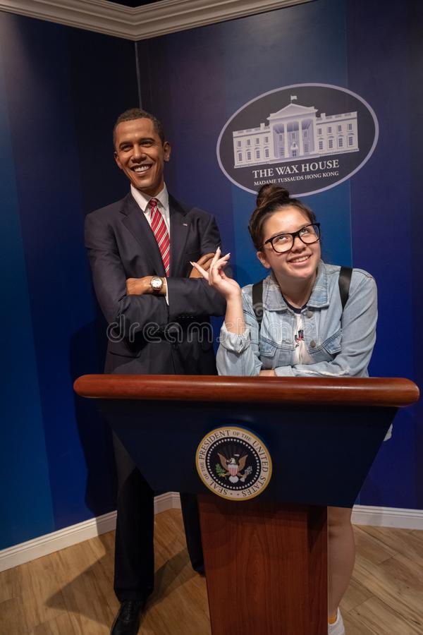 在蜡房子里, Barrack奥巴马总统与摆在作为秘书的一个女孩的,微笑得户内蜡博物馆 库存图片